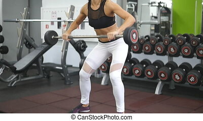 Young strong woman with perfect fitness body in sportswear snatches heavy weight in gym. Female bodybuilder doing exercise - practicing deadlift at club. Girl training - lifting barbell. Slow motion.