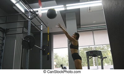 Young strong woman with perfect fitness body in sportswear exercising with medicine ball at gym. Girl doing crossfit training. Female athlete squats during workout indoor. Slow motion. Close up
