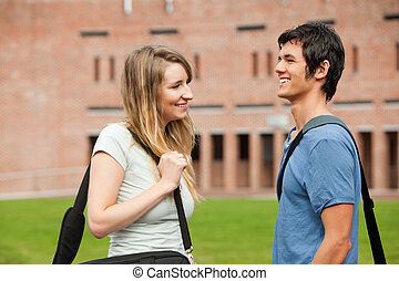 Young student couple flirting outside a building