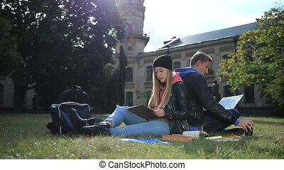 Young student couple studying in the park lawn