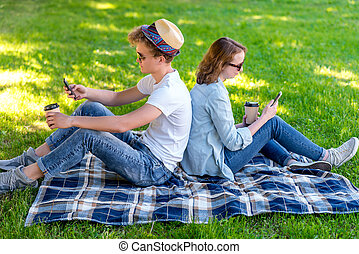 Young student girl and boy. They are sitting in park in nature. In the summer on a plaid. In hands of smart phones. Watching video on the phone. Camping. In hands of coffee mugs with hot coffee.