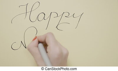 Young student girl hands with red nails writing happy new...