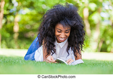 Young student girl reading a book in the school park - African people