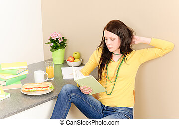 Young student girl reading book at home
