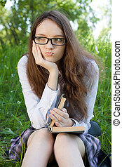 young student girl sitting in park with book