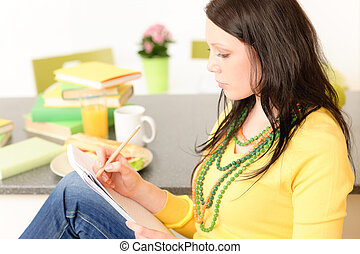 Young student girl thinking in kitchen