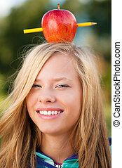 young student girl with apple on her head