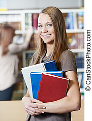 young student girl with book in library