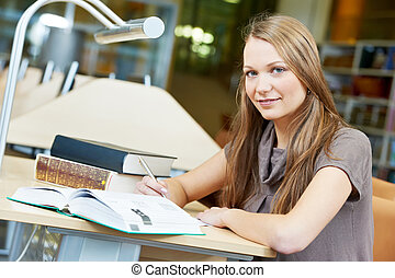 young student girl working with book at library