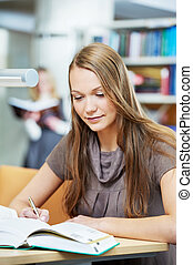 young student girl working with book in library