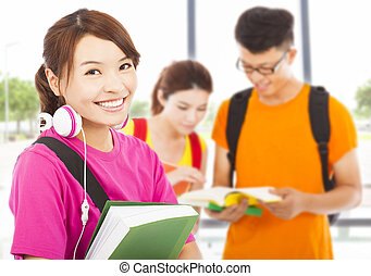 young student holding books and earphone with classmates