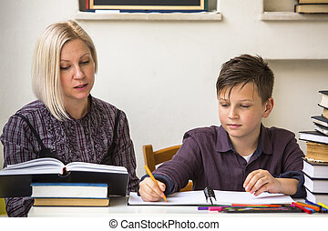 Young student learns at home with a his mom tutor.