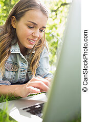 Young student lying on the grass using her laptop