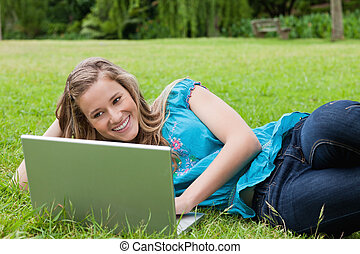 Young student lying on the side in a park while working on her laptop and smiling