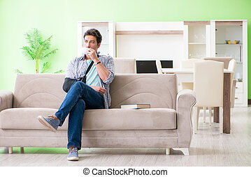 Young student man with hand injury sitting on the sofa