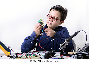 Young student performs experiments in electronics and dreams...
