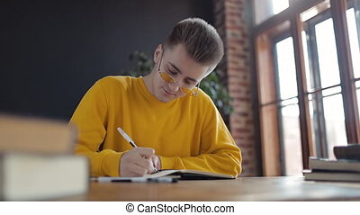 Young Student Thinking and Writing in Notebook - Young...