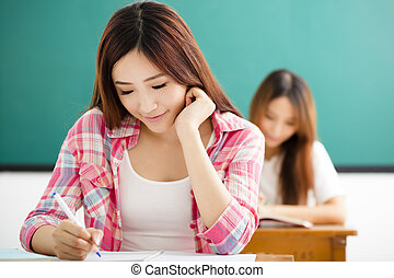 Young  student with others writing notes in the classroom