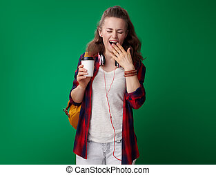 young student woman with coffee cup yawing isolated on green