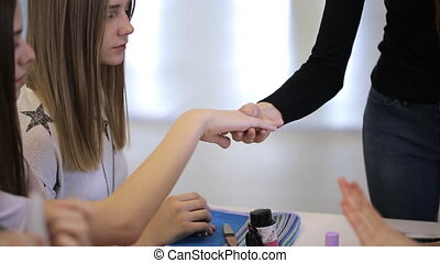 Young students demonstrate to their teacher grooming of their hands.