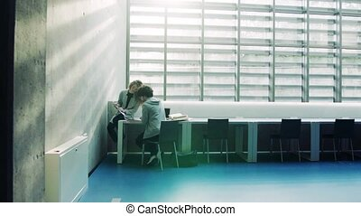 Young students in a library. - Young students studying in a...