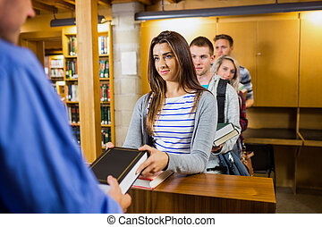 Young students in a row at the library counter