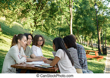 Young students sitting and studying outdoors while talking.