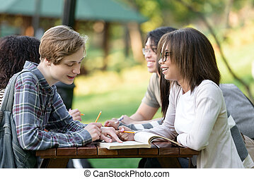Young students sitting and studying outdoors while talking