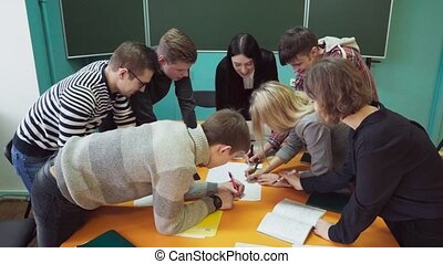 Young students with a teacher writing and discussing something in classroom