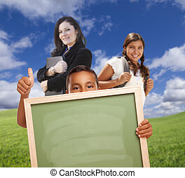 Young Students with Blank Chalk Board, Teacher Behind on Grass