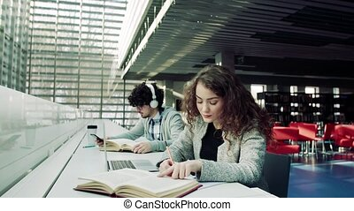 Young students with laptop and headphones in a library.
