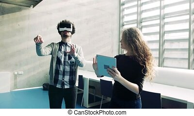 Young students with tablet and VR goggles in a library. -...