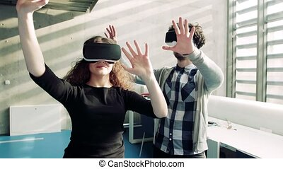 Young students with VR goggles in a library. - Portrait of ...