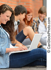 Young studying woman using laptop outside college