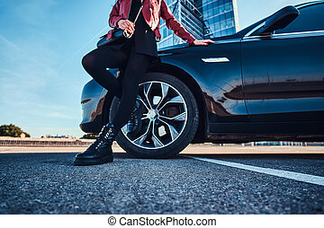 Young styilish woman is chilling in bright sunny day next to her car