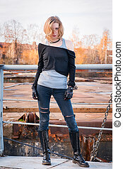 Young stylish aggressive looking woman. Lace-up boots, black leather gloves, ripped jeans, blond hair.