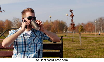 Young stylish and trendy man in black glasses sits on a bench drinking coffee and talking on the phone, close-up, copy space, slow motion, fashionable