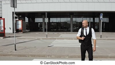 young stylish bald businessman comes out from business center, airport, office. Concept: a new business, traveling the world, communication, contacts, a new deal, success. back view