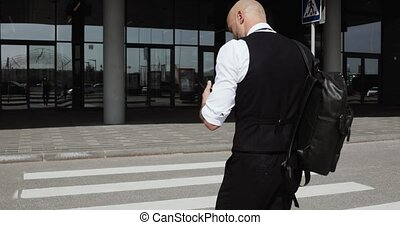young stylish bald businessman walking to business center,...
