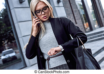 Young stylish blonde in glasses is late for a meeting. She speaks on the phone and looks at her wristwatch.
