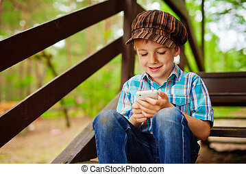 Young stylish boy browsing internet on mobile phone