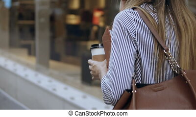 Young stylish businesswoman walking through the street with documents and coffee cup and using smartphone, talking with clients. Busy female working on the coffee break in downtown.