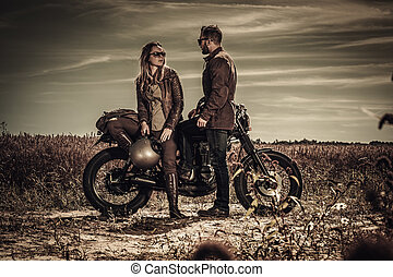 Young, stylish cafe racer couple on vintage custom motorcycles in field