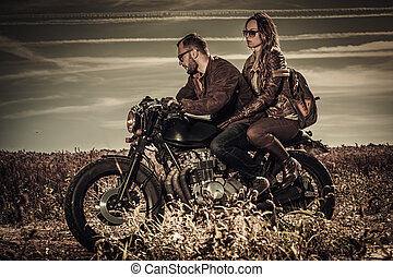 Young, stylish cafe racer couple on vintage custom...