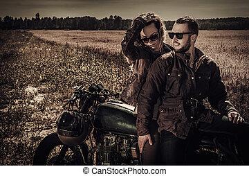 Young, stylish cafe racer couple on vintage custom...
