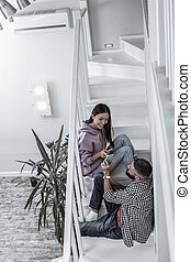 Young stylish couple sitting on stairs in their light spacious home