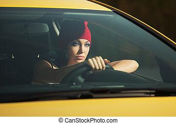 Young stylish fashion woman driving a car