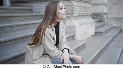 Young stylish female wearing jeans and coat smiling at ...