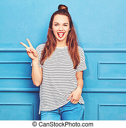 Young stylish girl model in casual summer clothes with red lips, posing near blue wall. Showing her tongue and peace sign