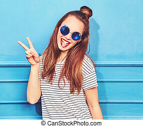 Young stylish girl model in casual summer clothes with red lips, posing near blue wall. Showing peace sign and her tongue